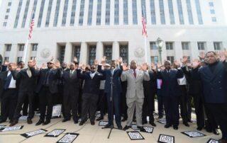 Black men with hands raised