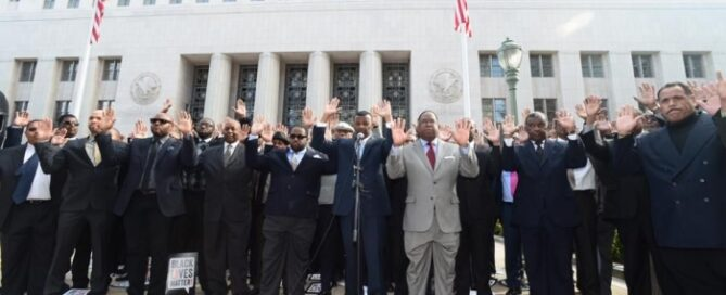 Black men with hands raised